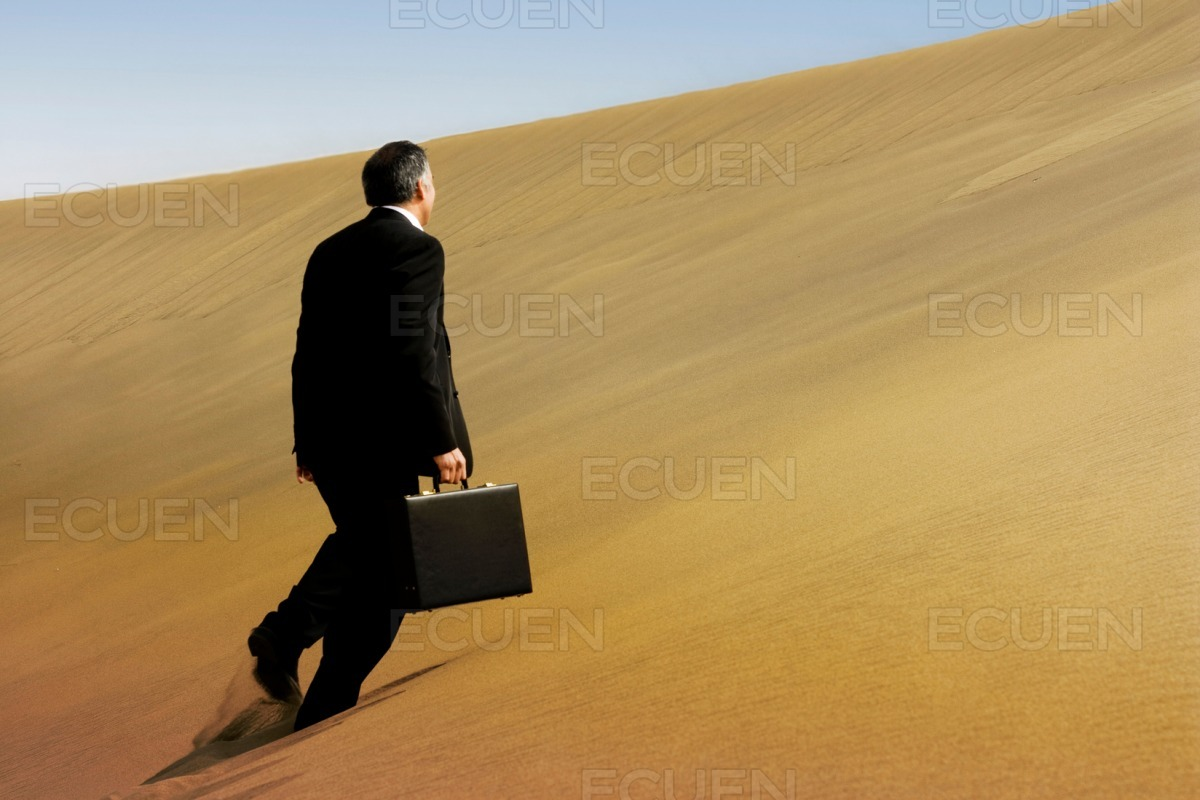 A business man running across the face of a dune on the desert stock photo