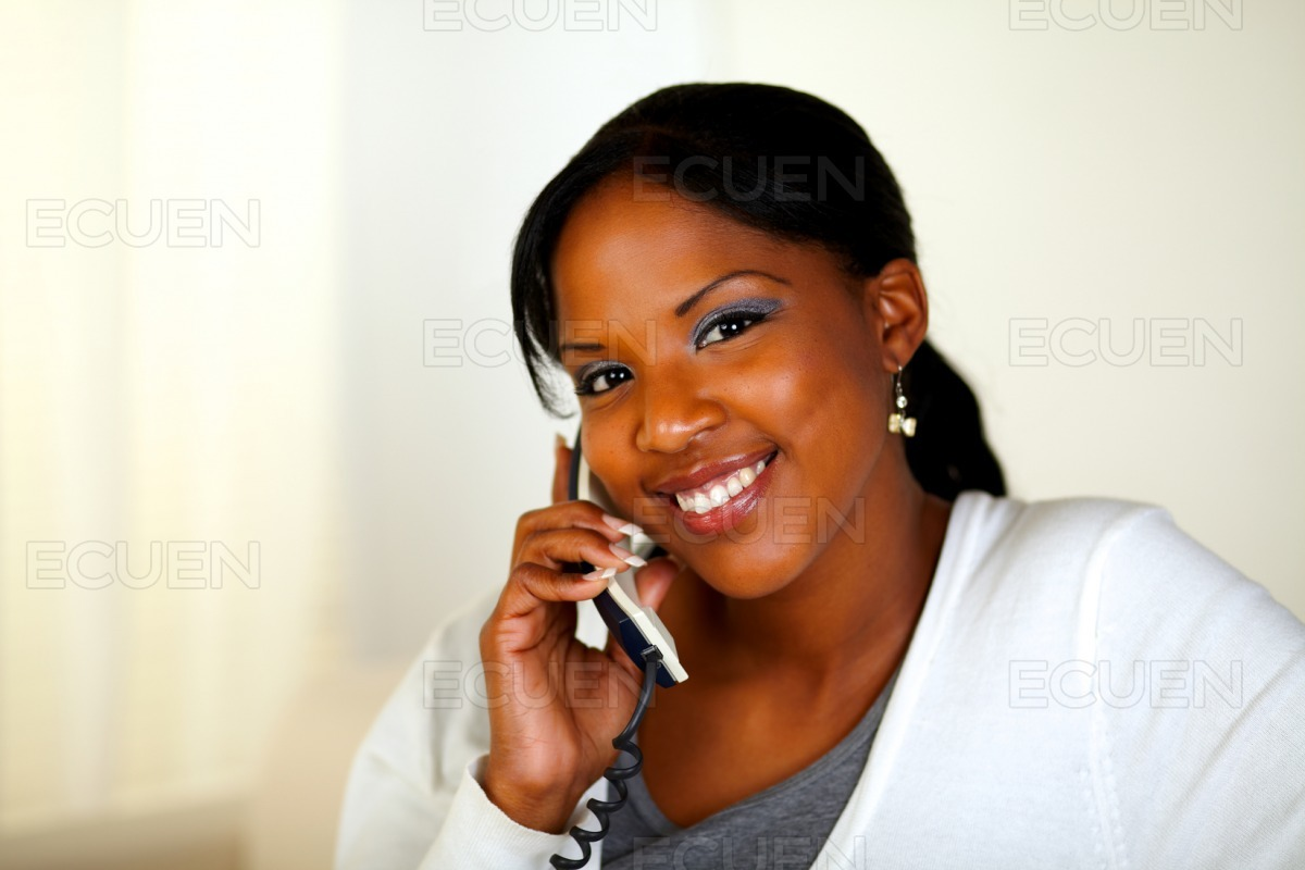 Afro-american woman looking at you on phone stock photo