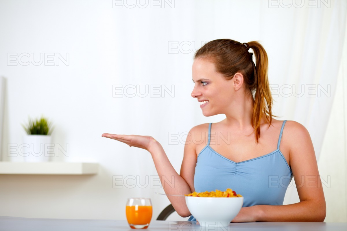 Beautiful blonde young woman eating breakfast stock photo