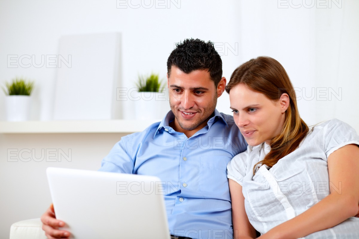 Beautiful young couple using laptop together stock photo