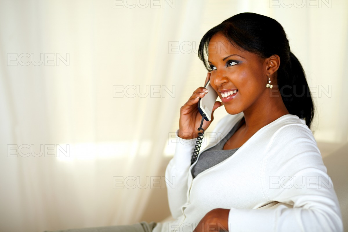 Beautiful young female smiling on phone stock photo