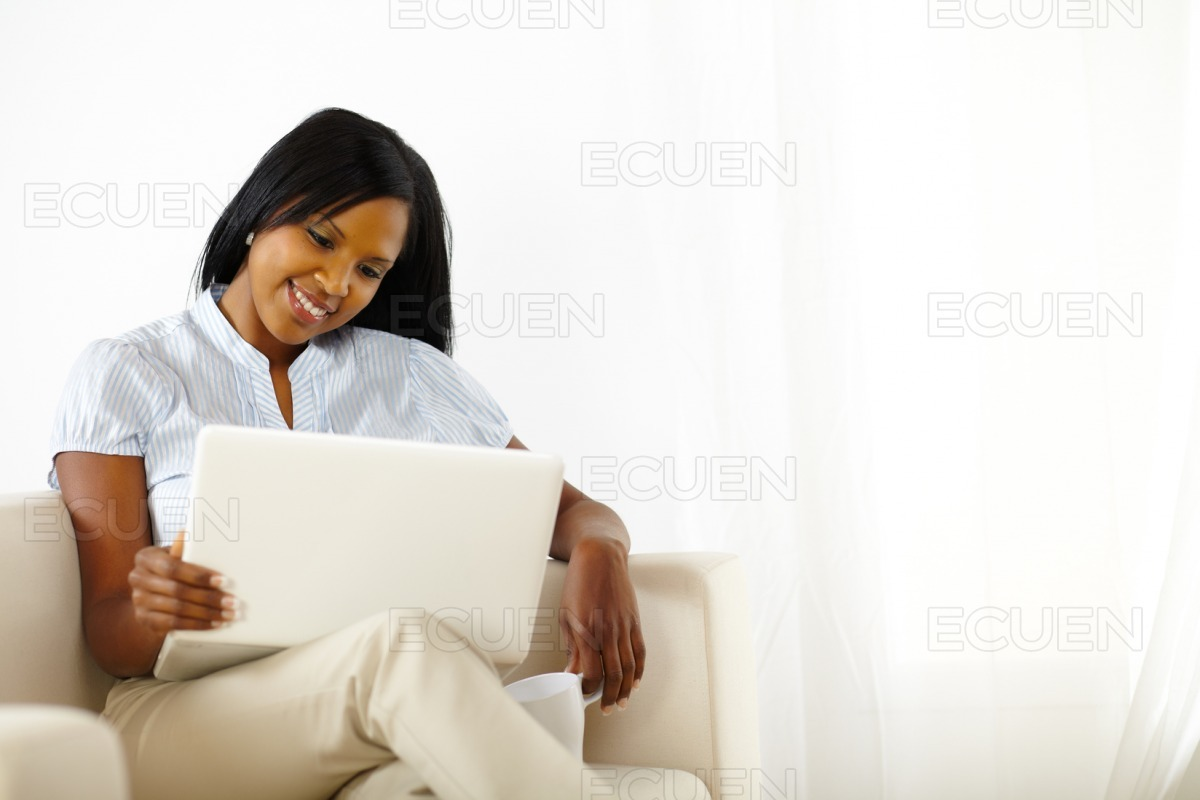 Calm young woman working on laptop stock photo