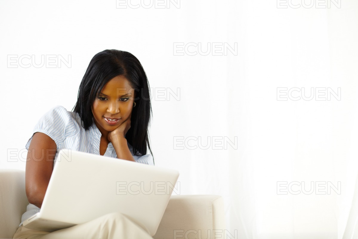 Calm young woman working on laptop at home stock photo