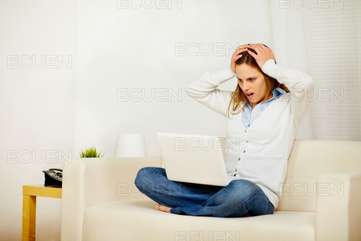 Casual woman working on sofa with a laptop stock photo