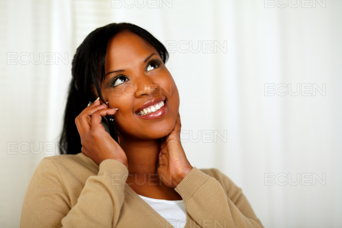 Charming girl looking up and conversing on mobile stock photo