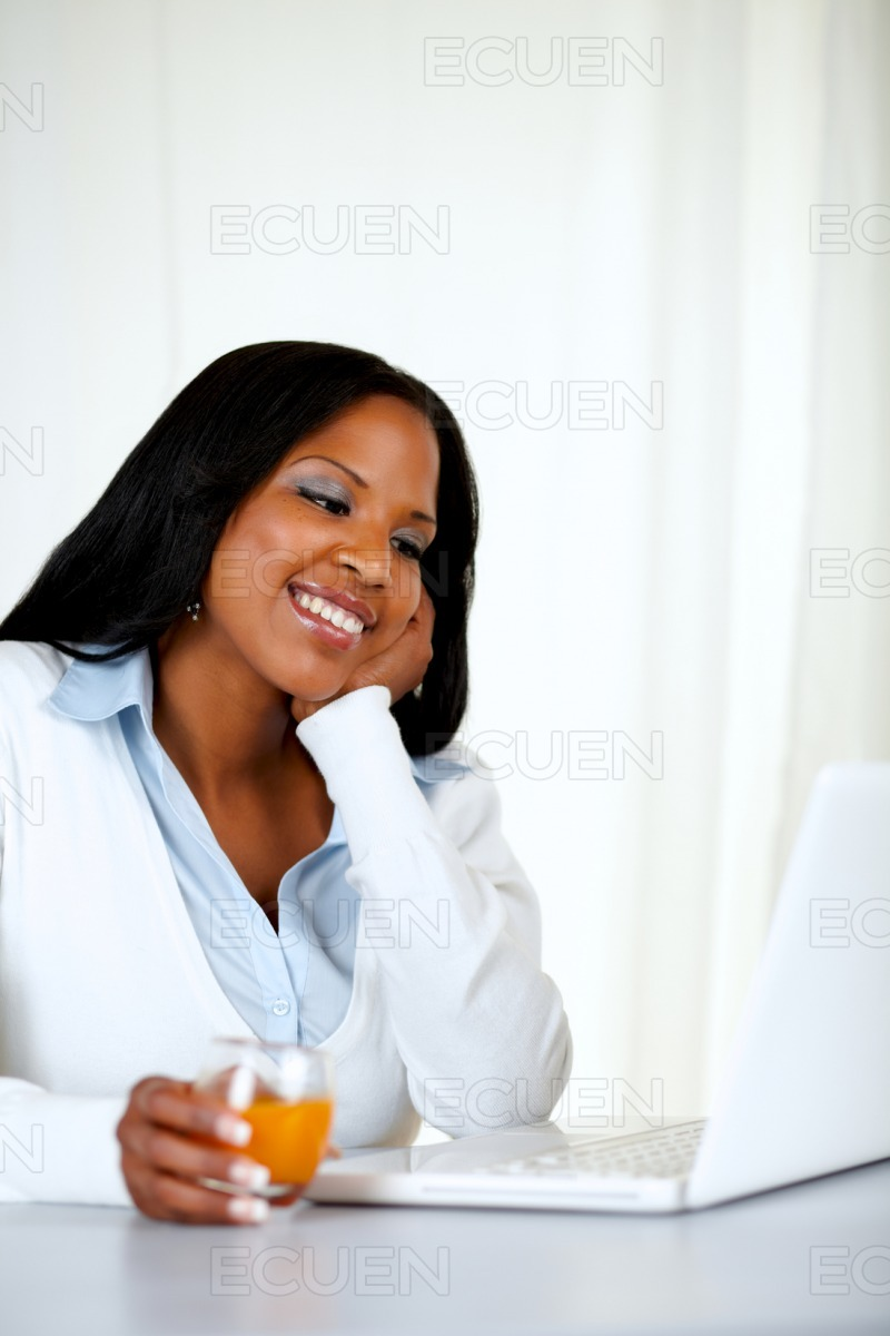 Charming woman smiling and reading on laptop stock photo