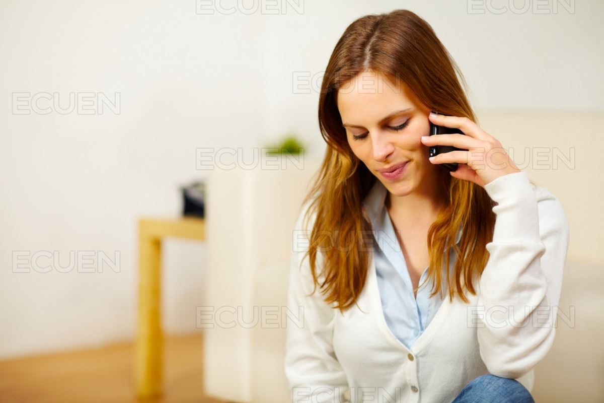 Charming woman speaking on the phone at home stock photo