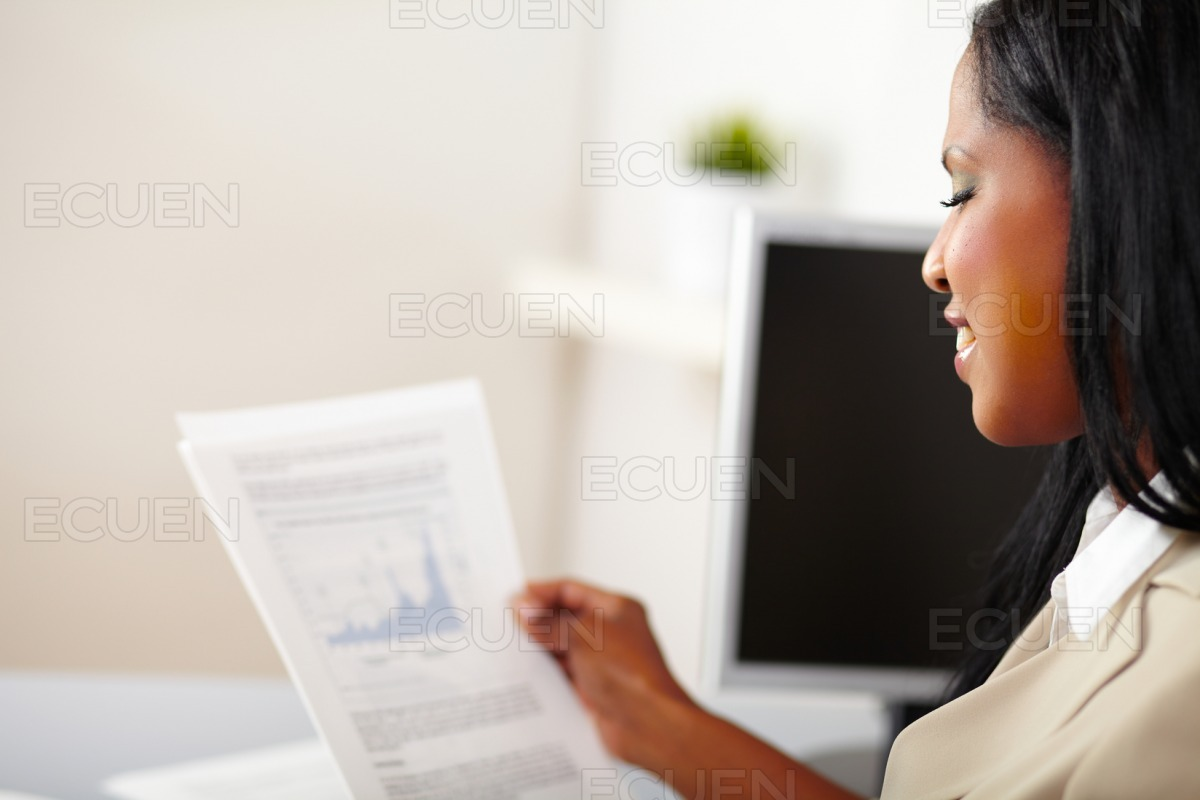 Cheerful business woman reading documents stock photo