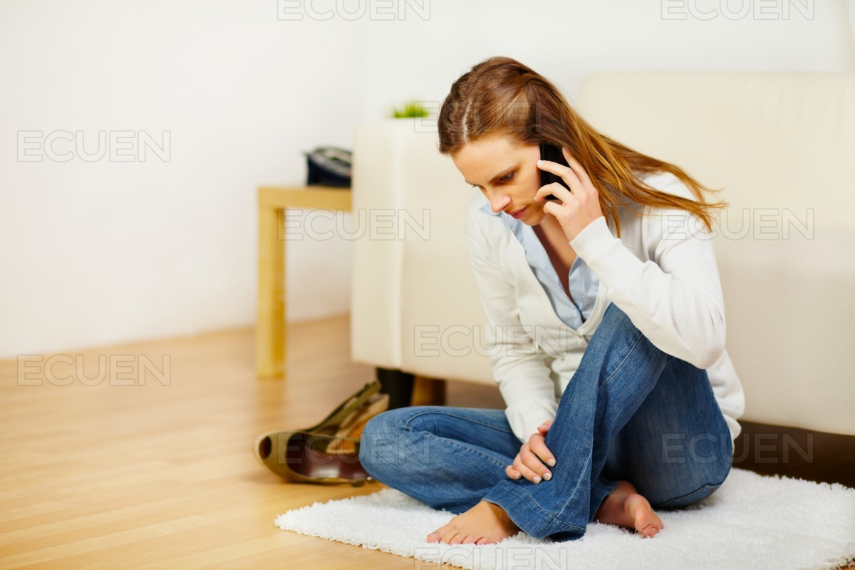 Cheerful woman talking on mobile phone at home stock photo