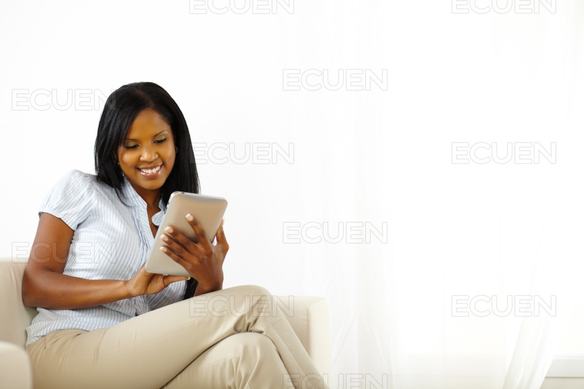 Cheerful young woman using a tablet PC stock photo