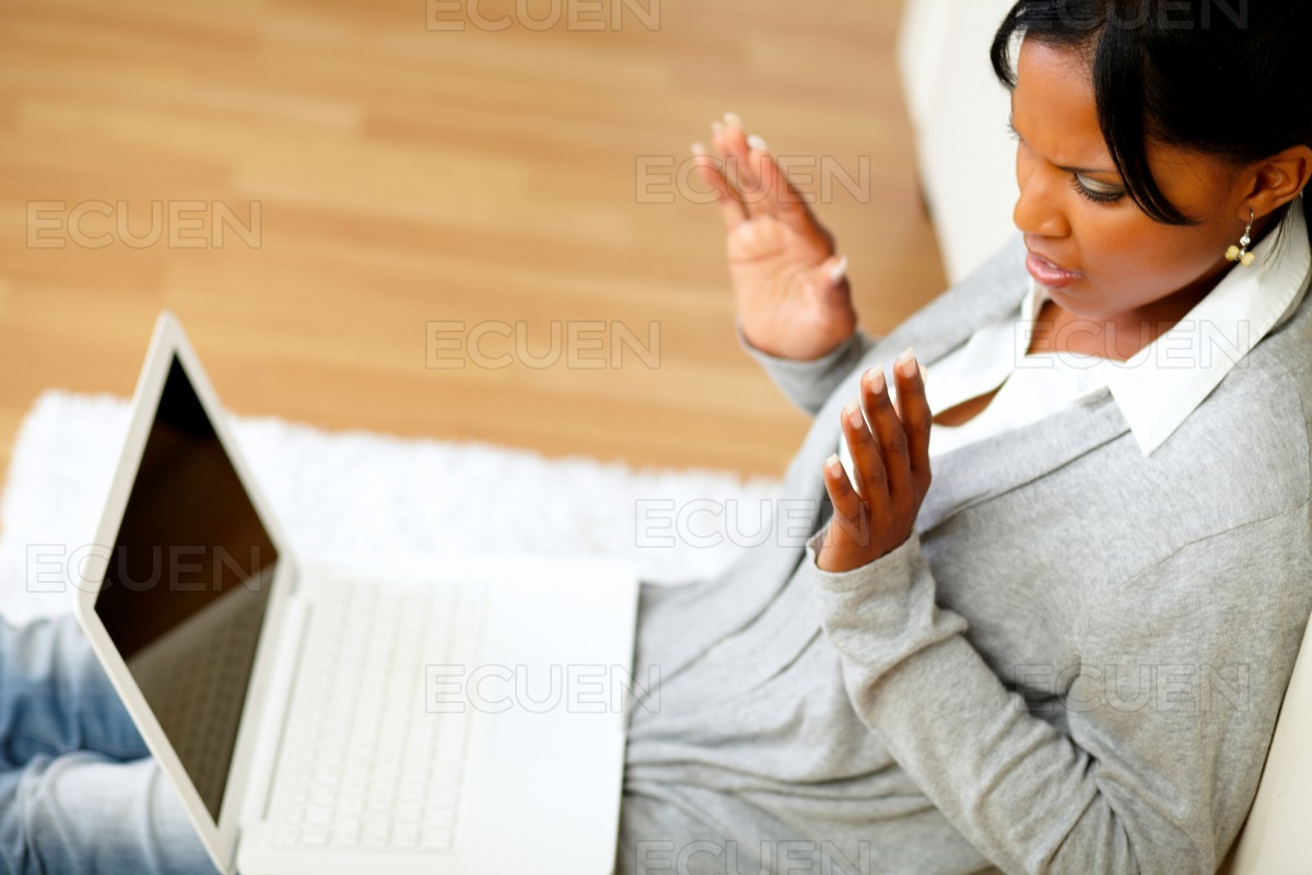 Confused young woman reading a message on laptop stock photo
