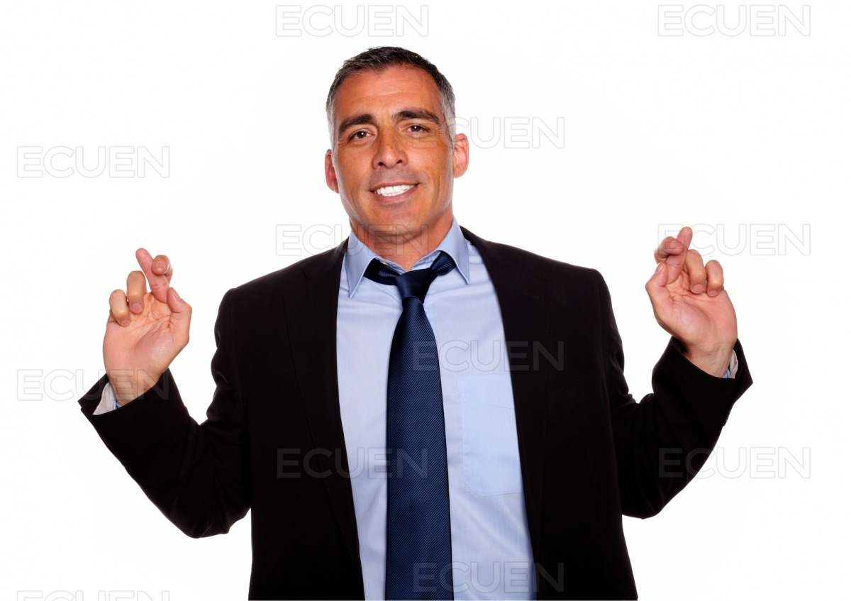 Executive man smiling and crossing the fingers stock photo
