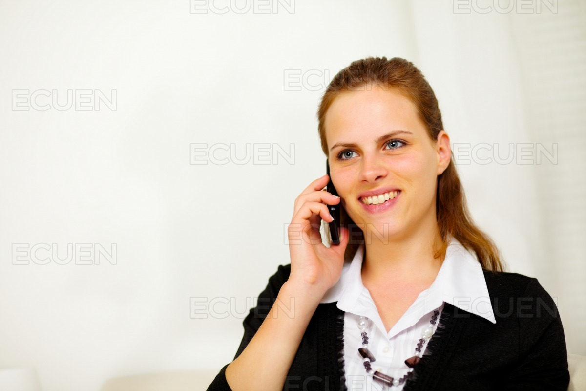 Friendly young businesswoman on mobile phone stock photo