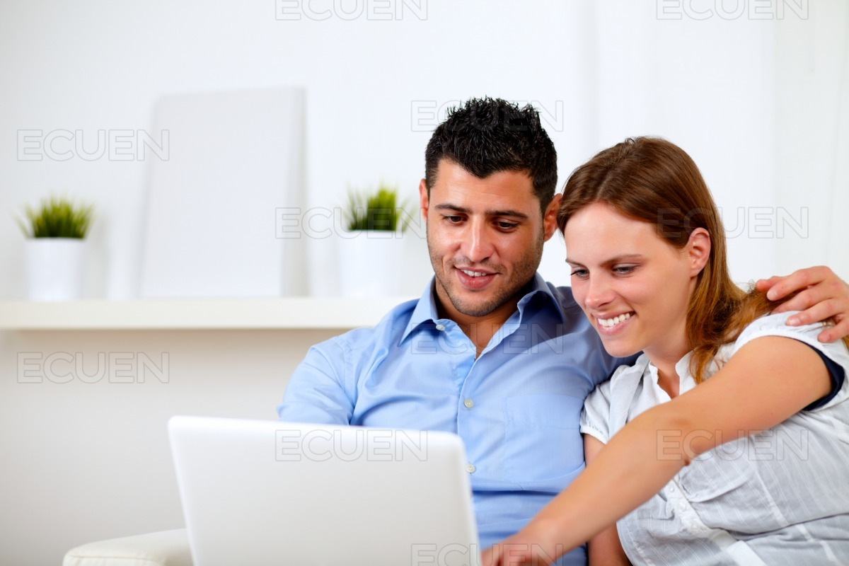 Friendly young couple using laptop together stock photo
