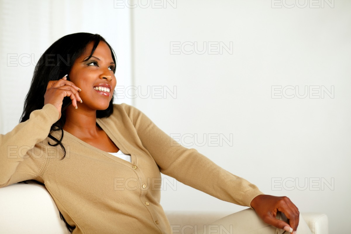 Friendly young woman looking up with cellphone stock photo