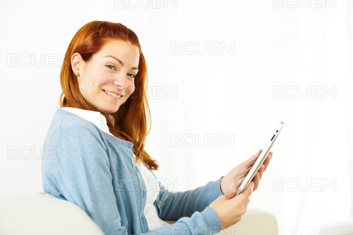 Friendly young woman working on tablet PC stock photo