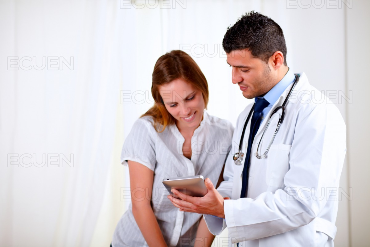 Handsome doctor and a female looking to tablet PC stock photo
