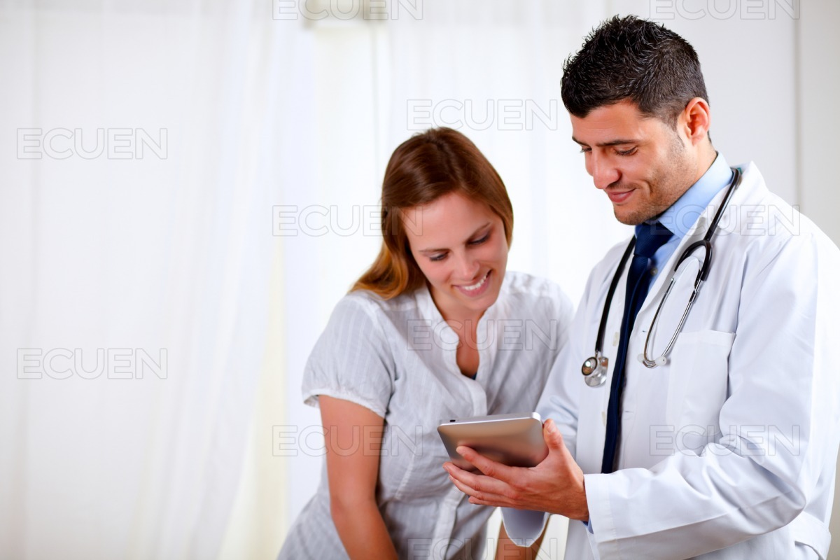 Handsome doctor and a woman looking to tablet PC stock photo