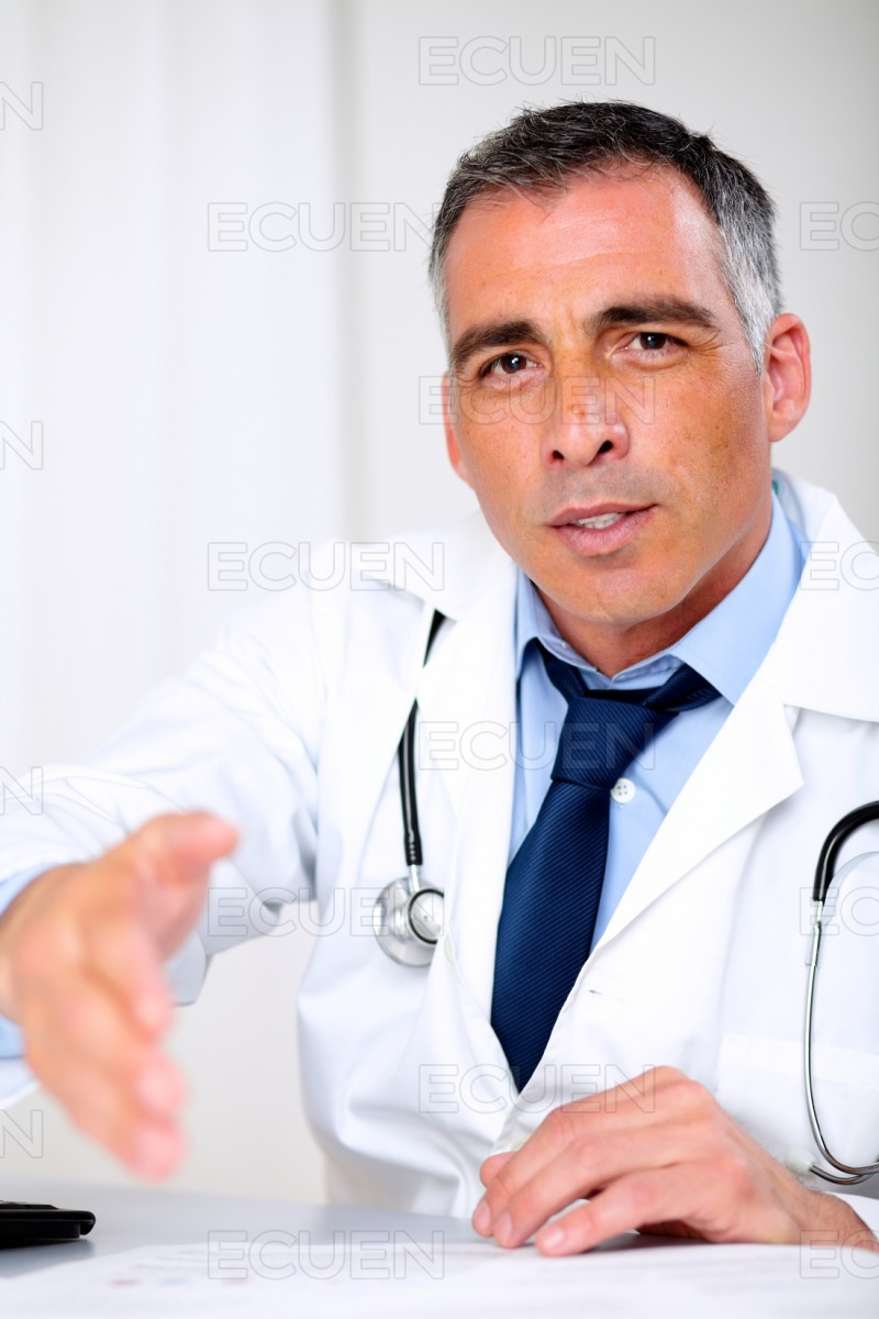Latin doctor greeting at the consultation desk stock photo