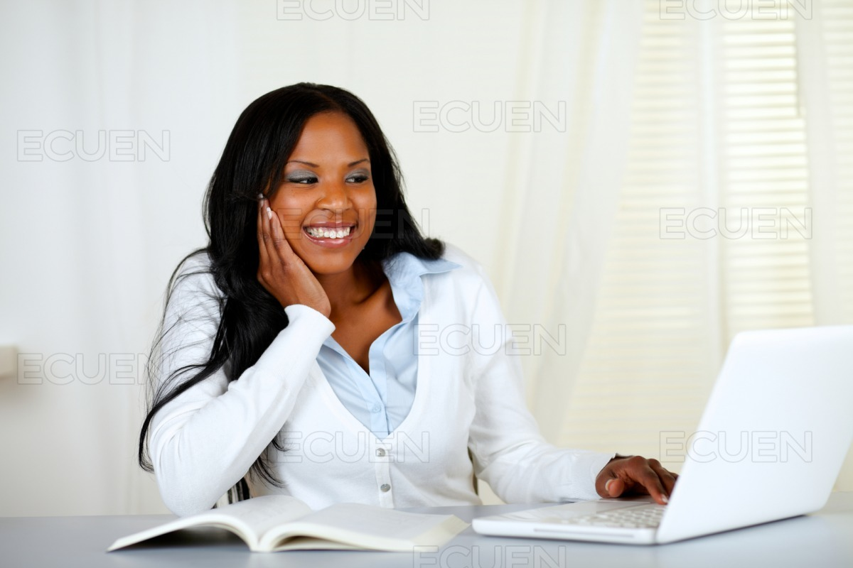 Lovely student woman smiling and looking to laptop stock photo