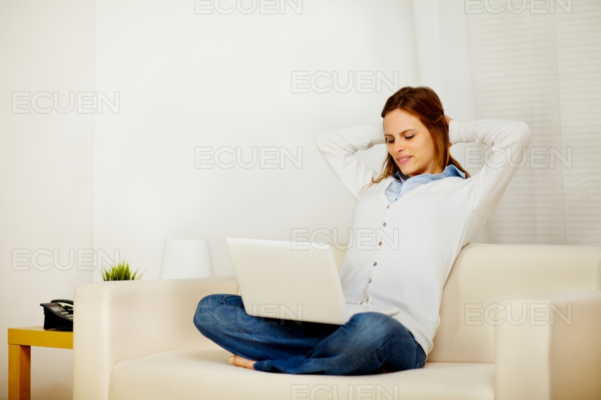 Lovely woman resting on sofa with a laptop stock photo