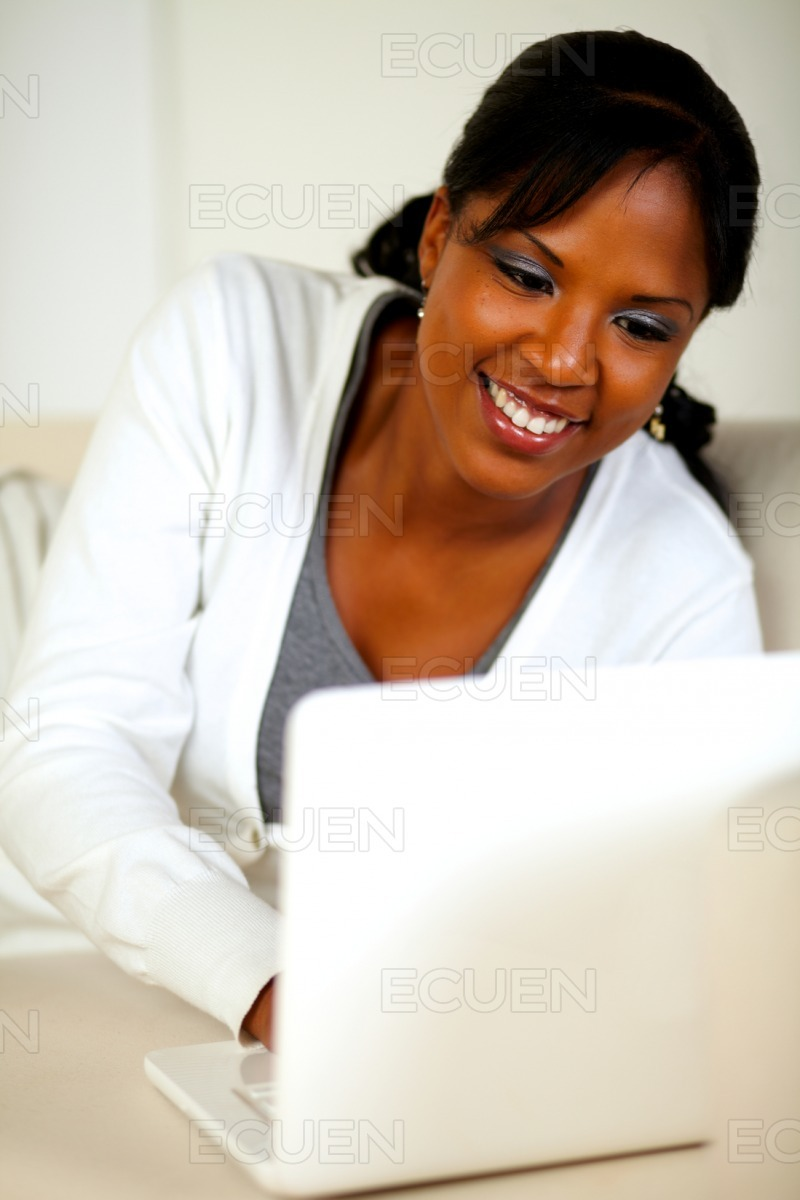 Lovely young female smiling and looking to laptop stock photo