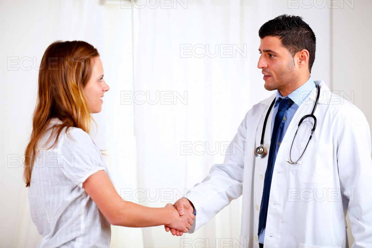 Medical specialist greeting a beautiful patient stock photo