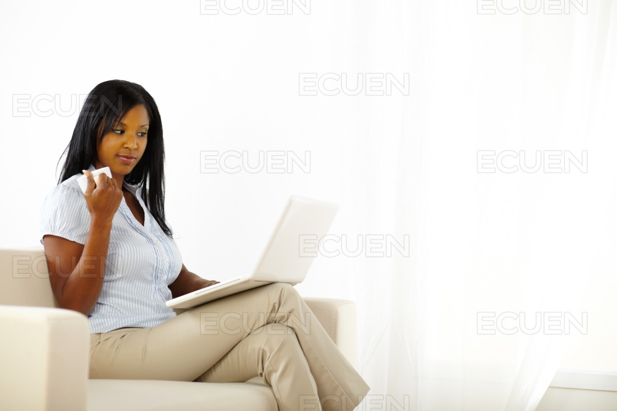 Mistrusted young woman working on laptop stock photo