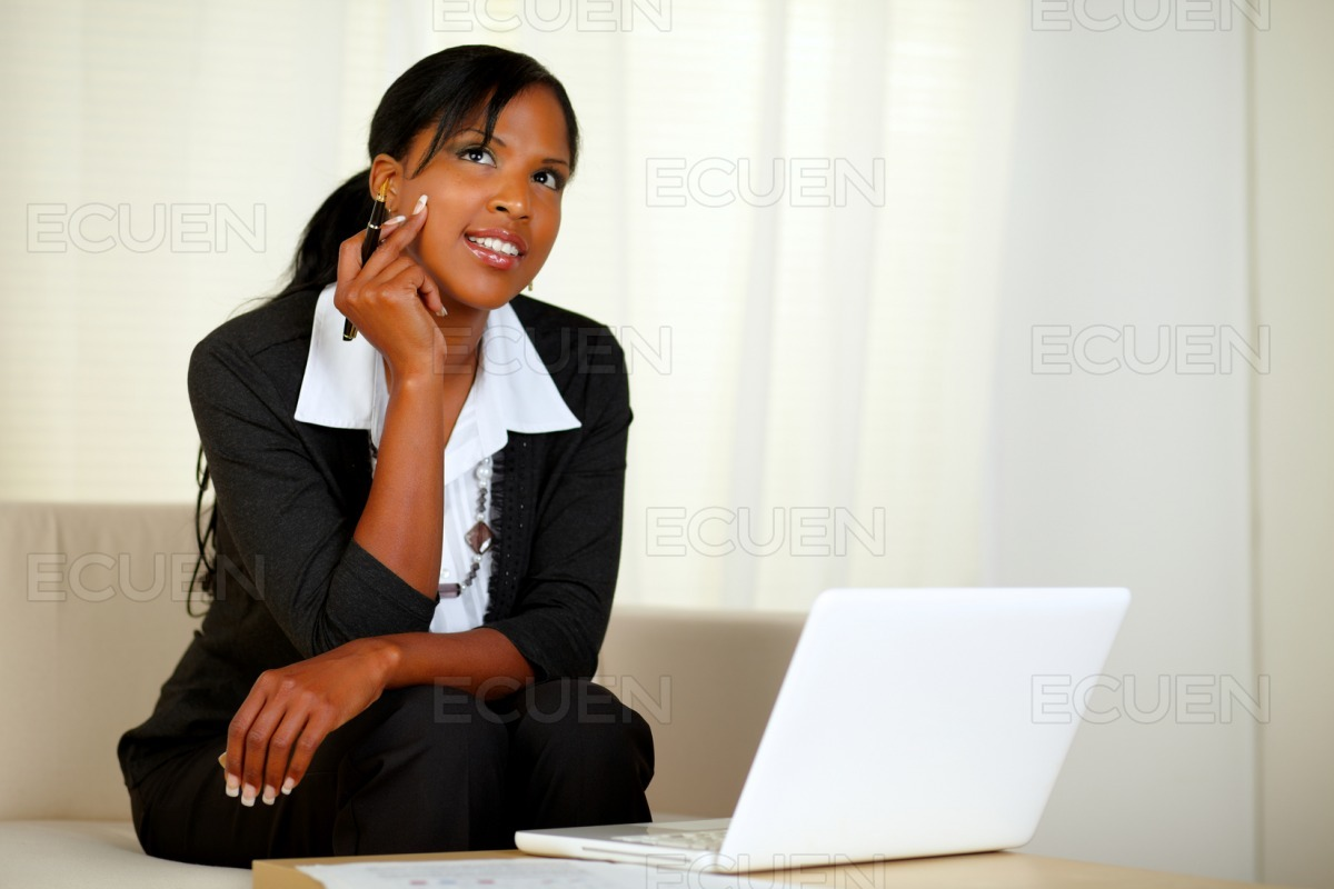 Pensive businesswoman with notes and laptop stock photo