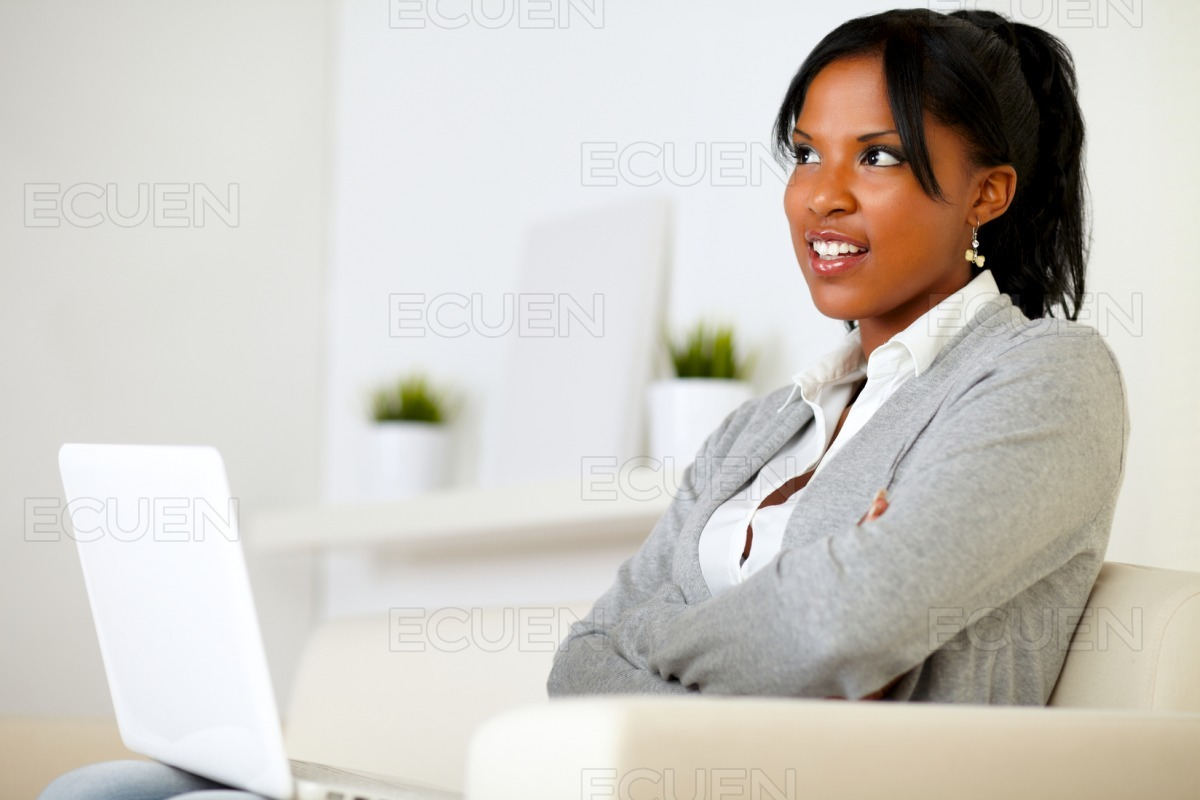Pensive young woman sitting on sofa with a laptop stock photo