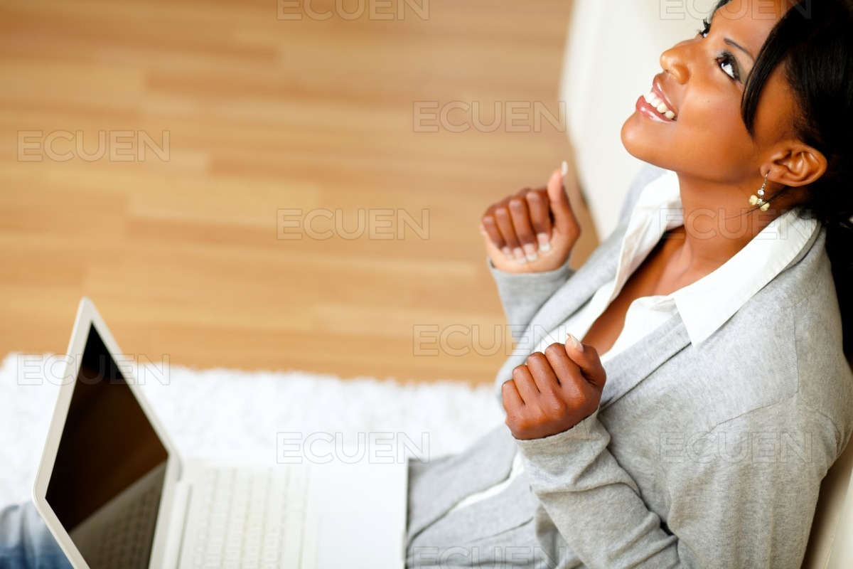 Positive afro-american young woman looking up stock photo