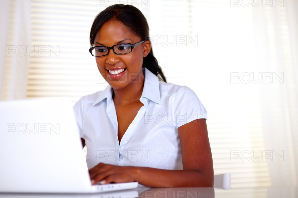Pretty female with black glasses working on laptop stock photo