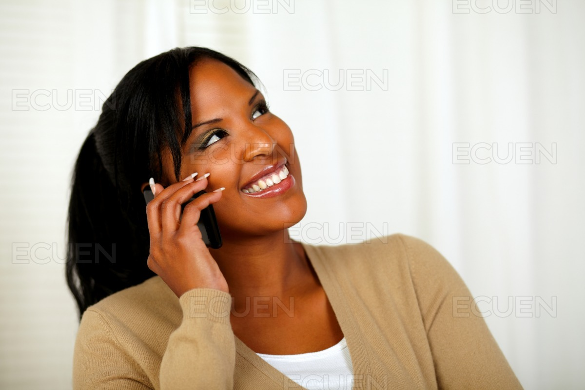 Pretty woman looking up while talking on cellphone stock photo