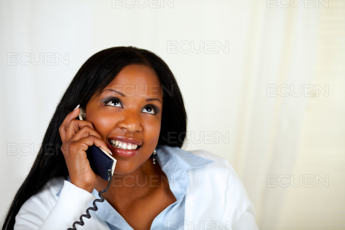 Pretty woman smiling and conversing on phone stock photo