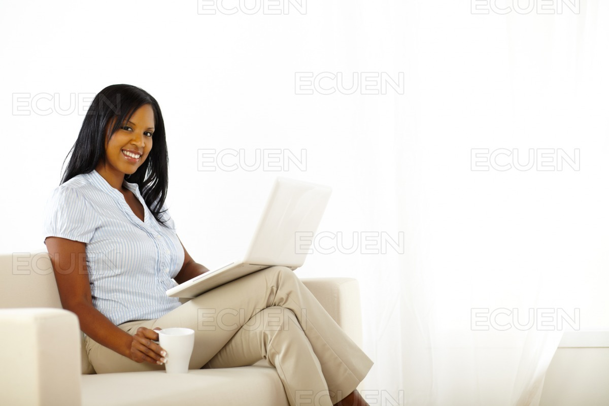 Pretty young woman working on laptop at home stock photo