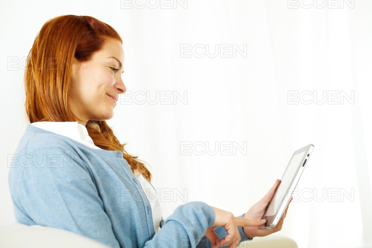 Quiet young woman working on tablet PC stock photo