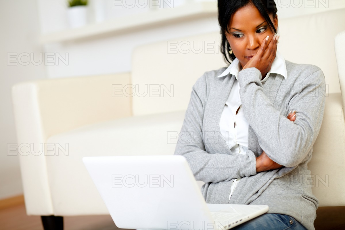 Reflective young woman reading something on screen stock photo
