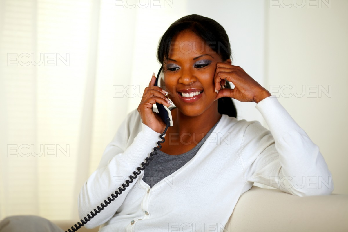 Relaxed young woman smiling and talking on phone stock photo
