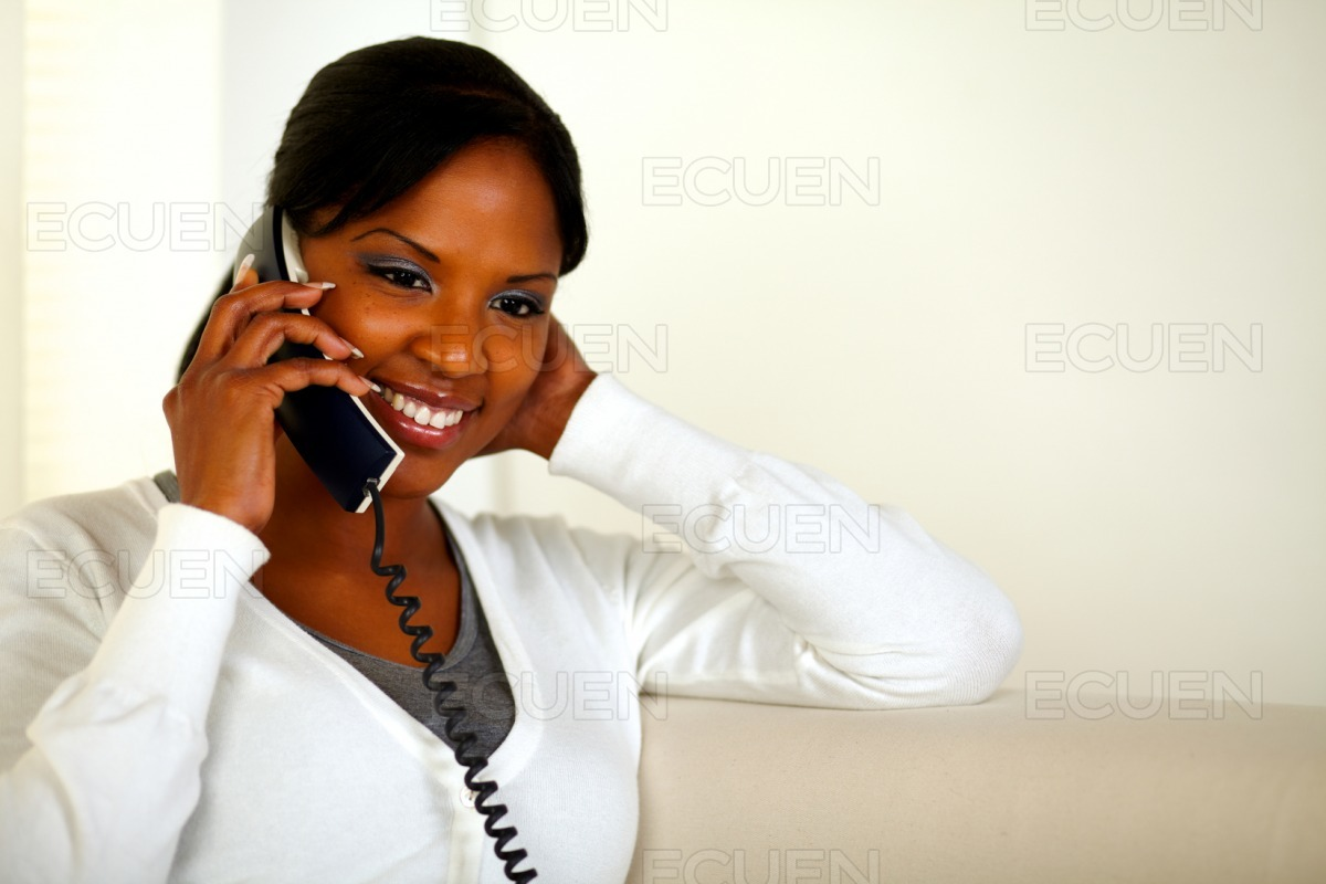 Smiling black woman talking on phone at home stock photo