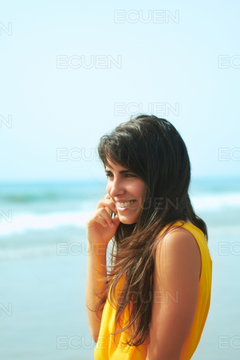 Smiling young lady talking on a cellphone stock photo
