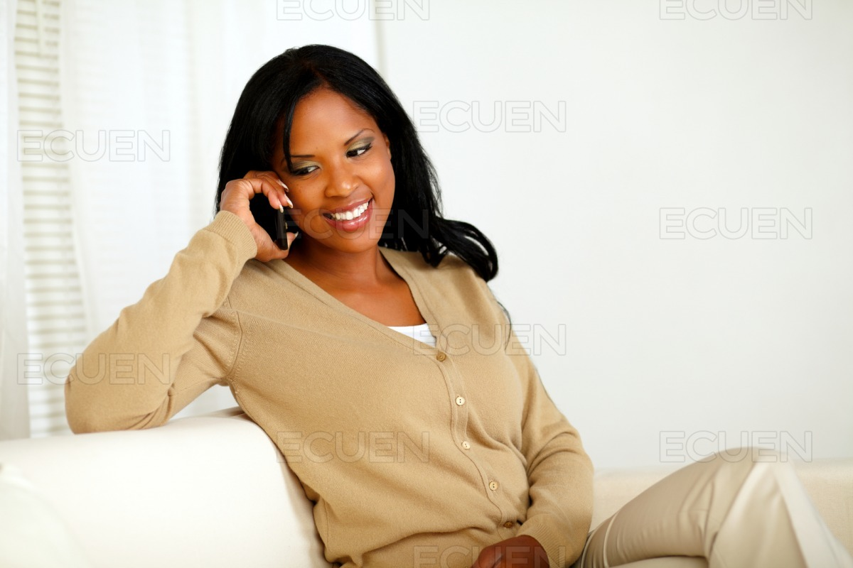 Smiling young woman talking on cellphone stock photo