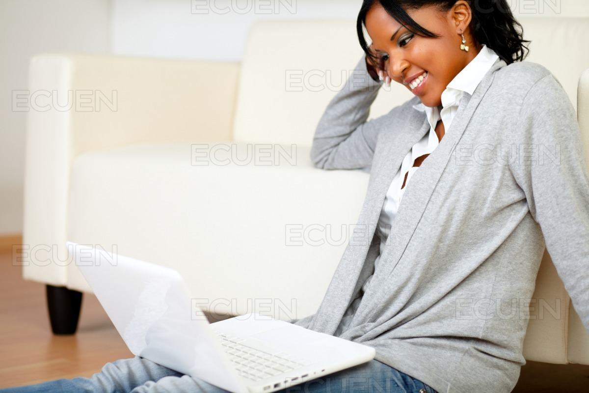 Smiling young woman working on laptop stock photo