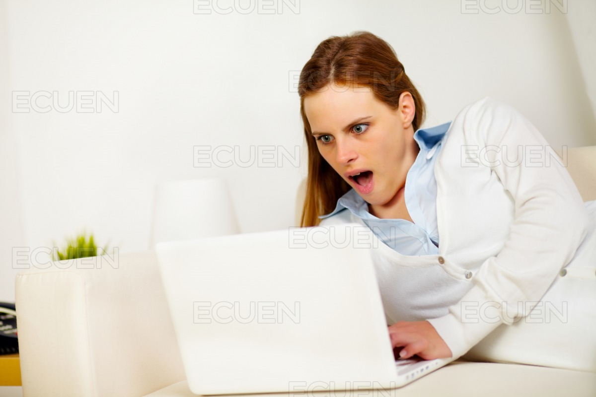 Surprised woman lying on sofa with a laptop stock photo