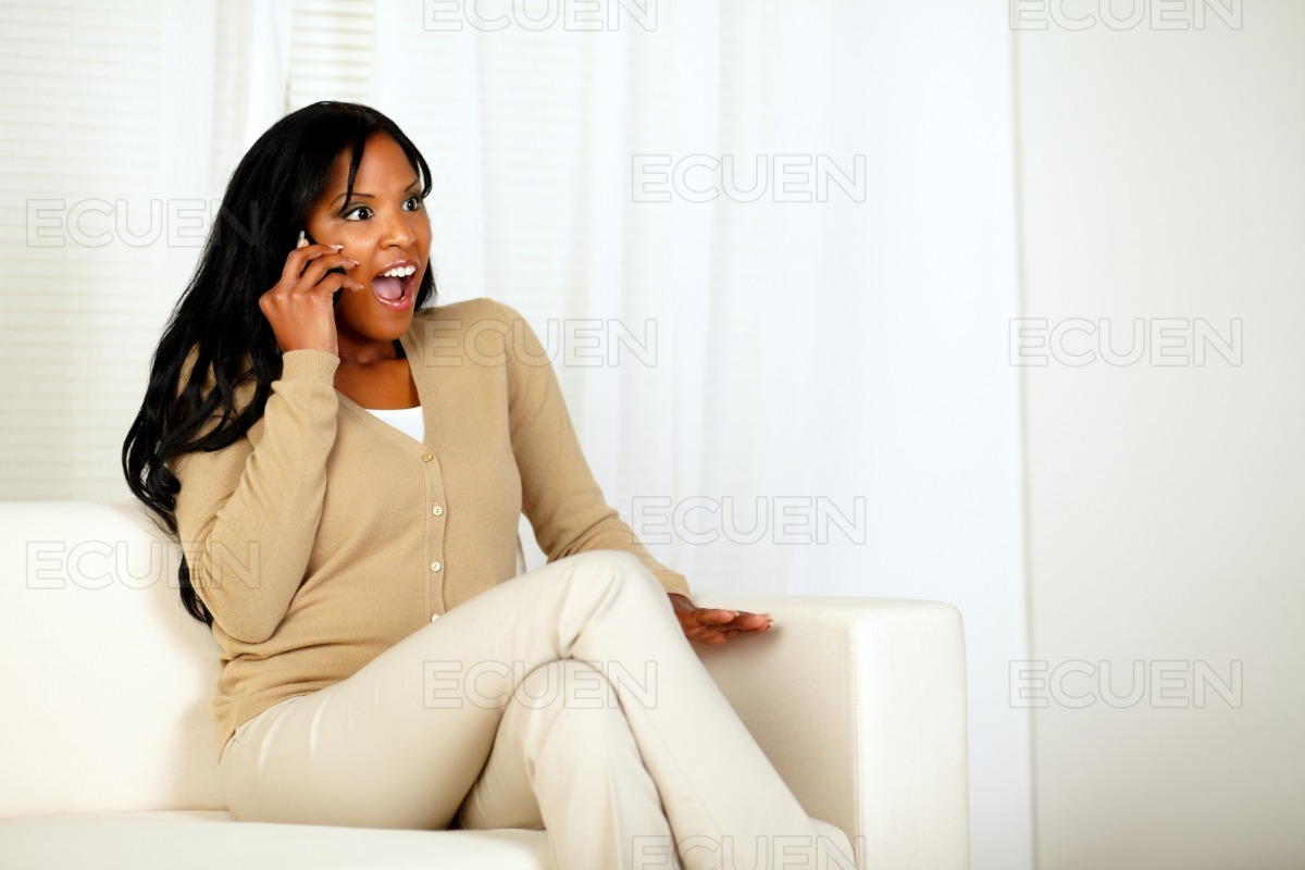Surprised woman sitting at home on sofa stock photo
