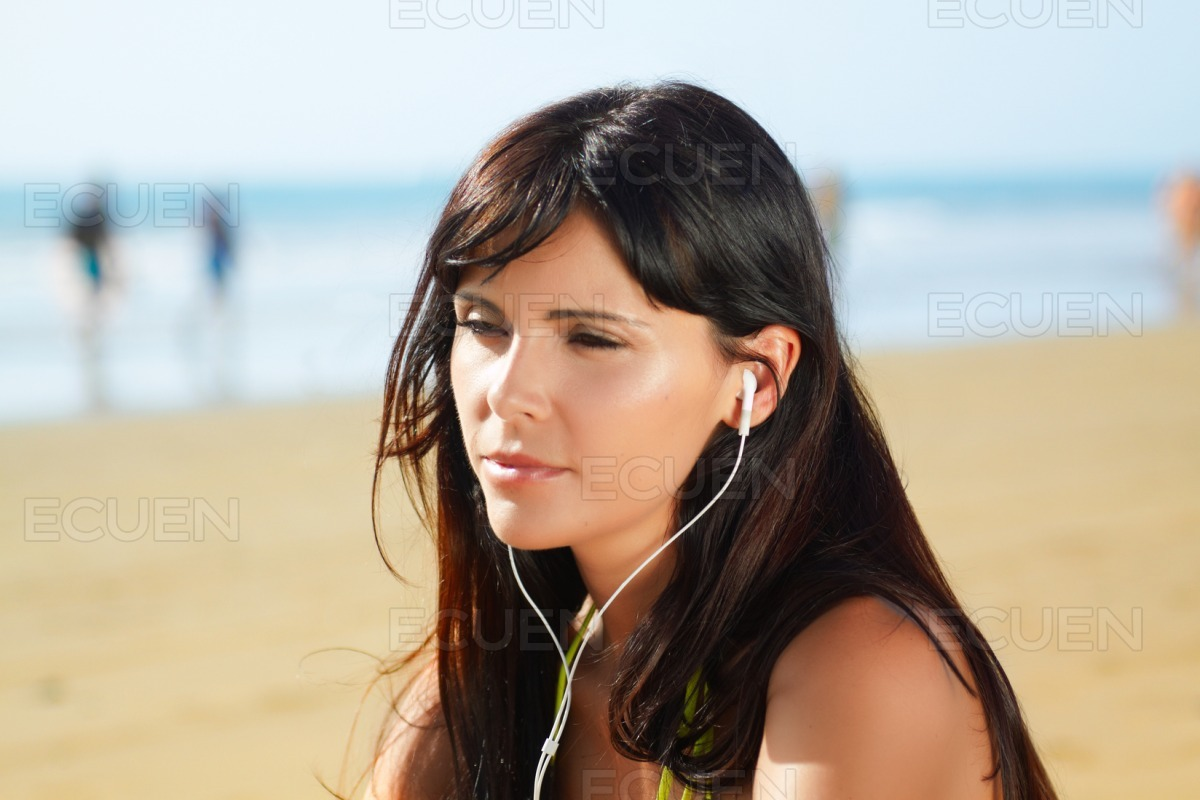 Woman on the beach listening to music stock photo