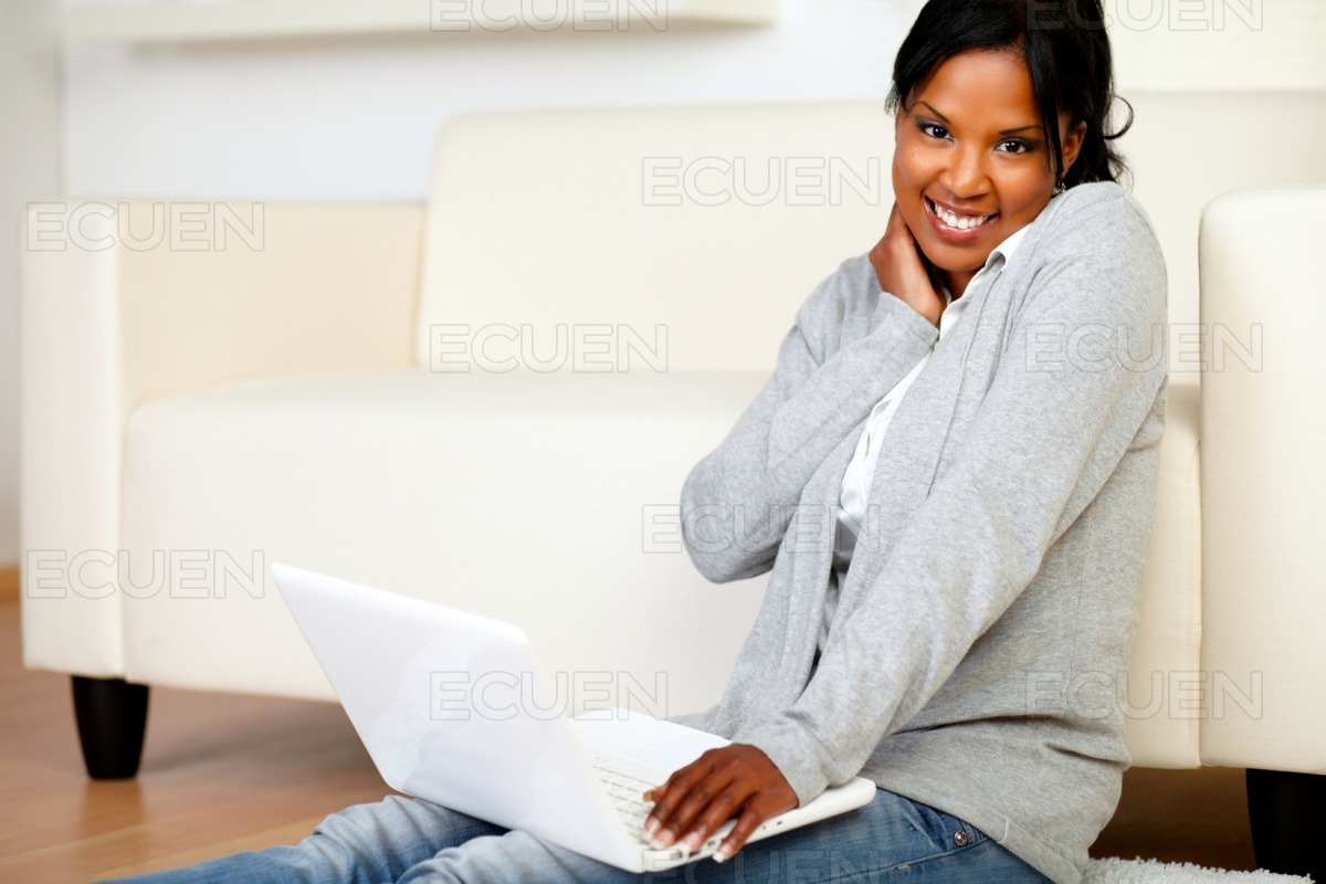 Woman smiling at you and browsing the Internet stock photo