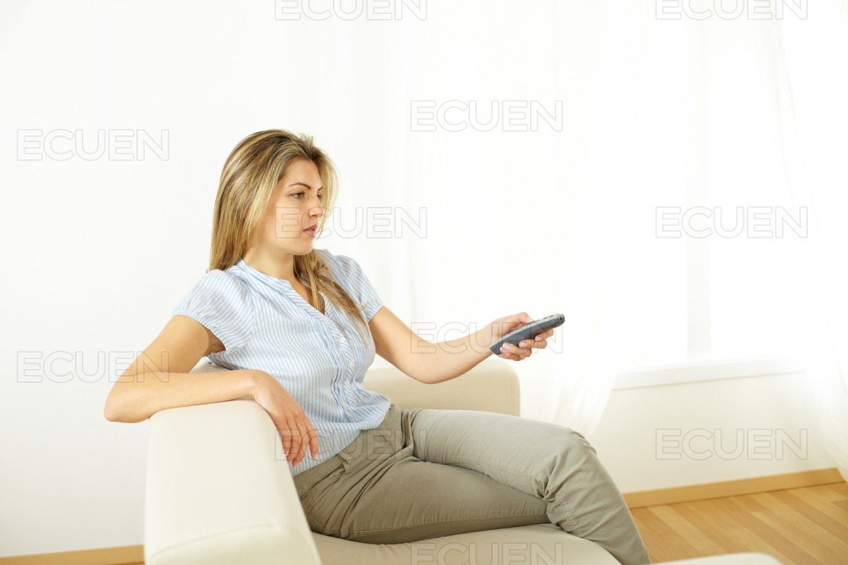Woman using a control remote stock photo