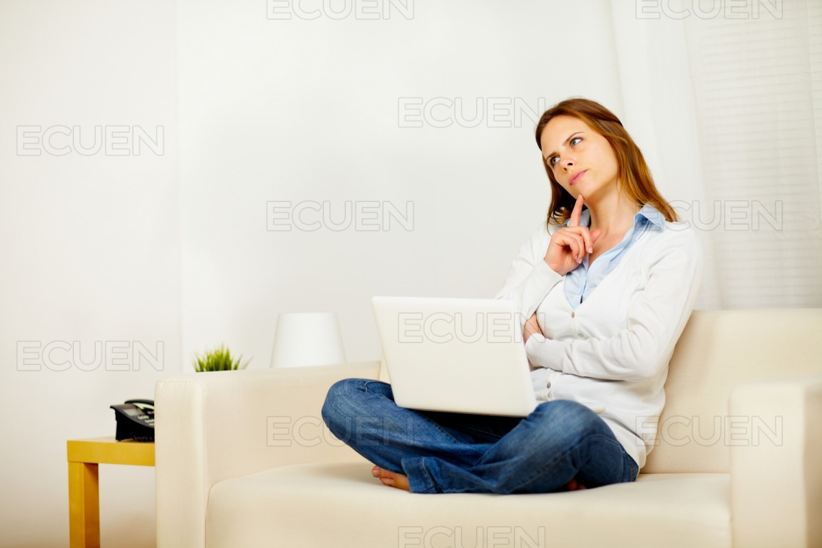 Young attractive woman thinking on sofa with a laptop stock photo