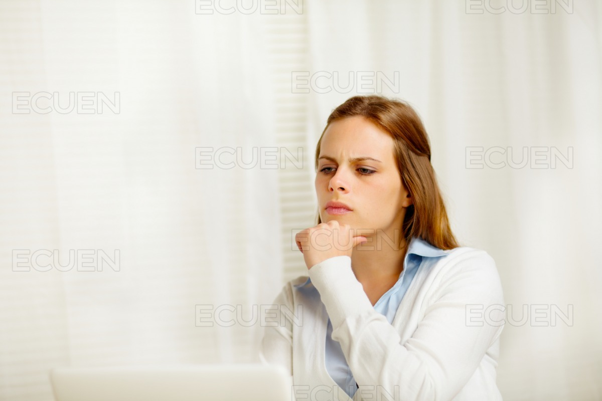 Young female thinking in from laptop stock photo