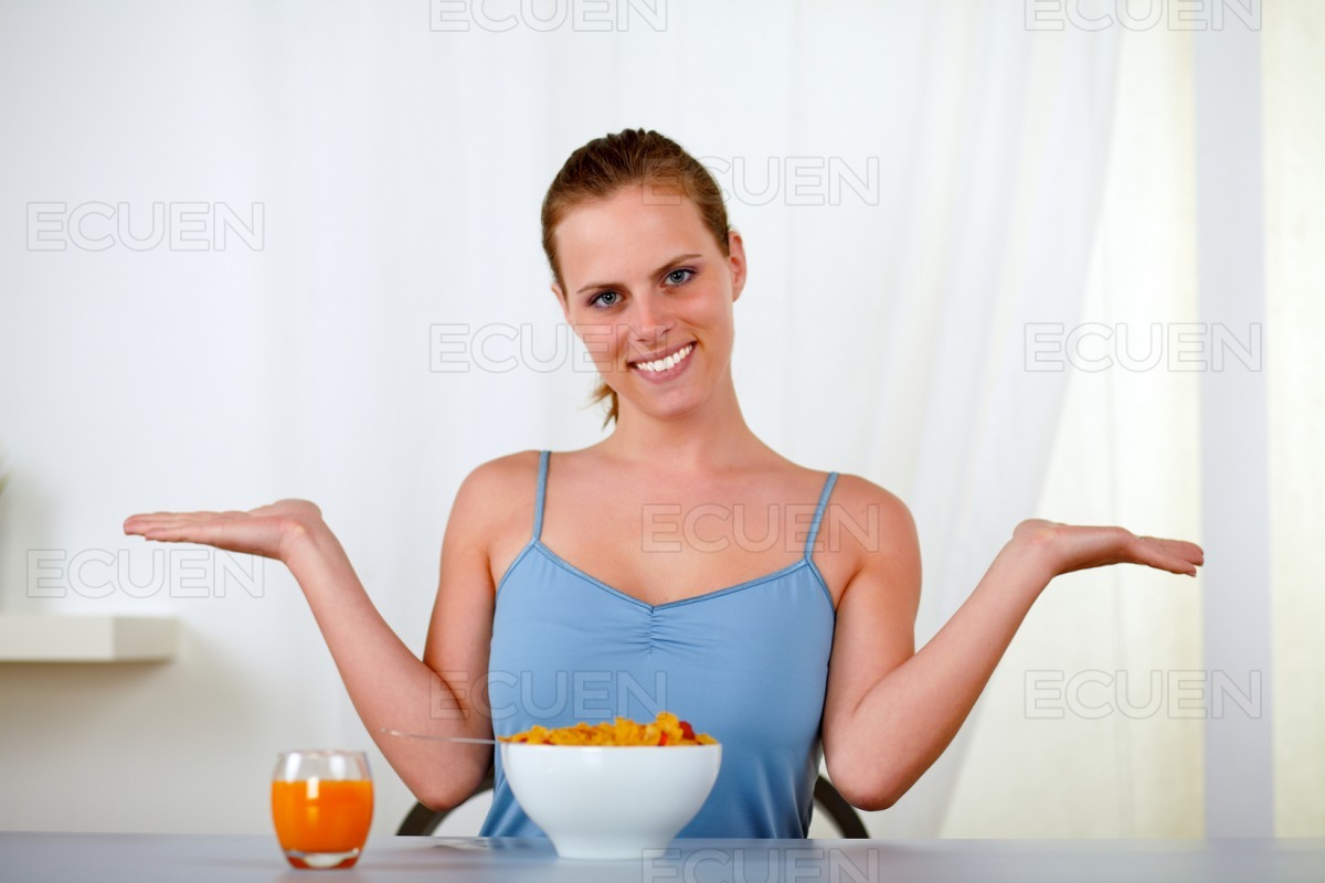 Young lovely woman eating healthy breakfast stock photo